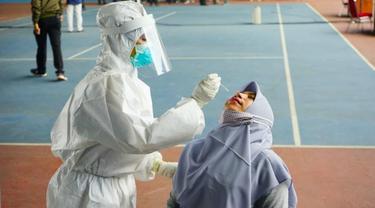 Petugas medis melakukan tes usap atau swab kepada warga di Pekanbaru untuk mendeteksi Covid-19.