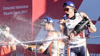 Pembalap Spanyol Repsol Honda, Marc Marquez (kanan) dan pembalap Dani Pedrosa (tengah) merayakan kemenangannya di atas podium pada balapan MotoGP Grand Prix Valencia di Sirkuit Ricardo Tormo, Valencia (12/11). (AFP PHOTO / Jose Jordan)