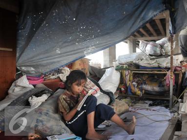 Seorang anak terlihat belajar meski dengan kondisi tempat tinggal yang memperihatinkan, Jakarta, Jumat (16/9). Sebelumnya, 50 bangunan liar di bawah kolong Tol Sedyatmo, Penjaringan kembali ditertibkan Pemkot Jakut. (Liputan6.com/Yoppy Renato)