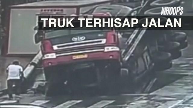 Sebuah truk tampak masuk ke dalam lubang yang muncul tiba-tiba