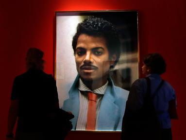 Pengunjung melihat karya seni seniman Hank Willis Thomas yang dipajang pada pameran 'Michael Jackson: On The Wall' di National Potrait Gallery, London, Rabu (27/6). Pameran ini berlangsung dari 28 Juni hingga 21 Oktober 2018. (AP/Kirsty Wigglesworth)