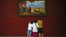 "Keluarga melihat lukisan minyak di atas kanvas yang berjudul ""Upacara Pendirian Tiongkok"" oleh Dong Xiwen, ketika mereka mengunjungi Museum Nasional Cina di Beijing (22/8/2019). Museum ini dibangun oleh Kementerian Kebudayaan Republik Rakyat Tiongkok. (AFP Photo/Wang Zhao)"