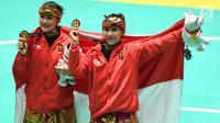 Pasangan pesilat Indonesia, Ayu Sidan Wilantari dan Ni Made Dwiyanti membentangkan bendera merah putih saat merayakan kemenangan usai meraih medali emas nomor seni ganda putri di Padepokan Pencak Silat (TMII, Rabu (29/8). (Merdeka.com/ Imam Buhori)