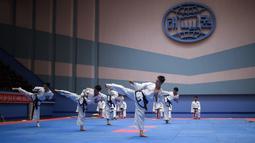 Peserta melakukan tendangan selama demonstrasi taekwondo sebagai bagian dari Kejuaraan Seni Bela Diri Nasional tahunan Mangyongdae di 'Taekwon-Do Hall' di Pyongyang, Korea Utara (9/11). (AFP Photo/Kim Won Jin)