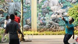 Warga berolahraga bulutangkis di sekitar kawasan Kebun Binatang Ragunan, Jakarta, Minggu (9/10). Kawasan KBR menjadi salah satu lokasi alternatif warga Jakarta untuk berolahraga pada Minggu pagi. (Liputan6.com/Helmi Fithriansyah)
