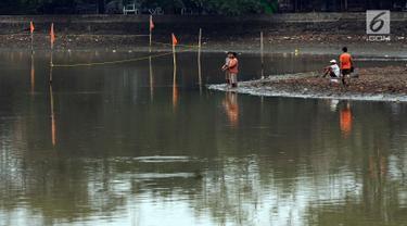Warga memancing di tengah Setu Babakan yang sedang surut, Jakarta, Jumat (7/7). Menurut petugas, air sengaja disurutkan terkait proyek pengerukan di sekitar hulu Setu Babakan. (Liputan6.com/Helmi Fithriansyah)
