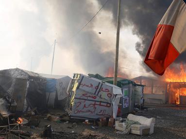 """Sebuah bendera Prancis berada di dekat Kobaran api yang membakar sebuah kamp pengungsian imigran selama pembongkaran kamp pengungsian imigran """"Jungle"""", di kota pelabuhan Calais, Prancis (26/10). (REUTERS/Pascal Rossignol)"""