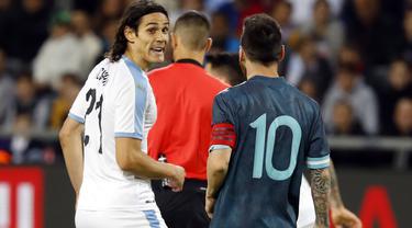 Megabintang timnas Argentina, Lionel Messi berbicara dengan penyerang timnas Uruguay, Edinson Cavani pada laga persahabatan di Stadion Bloomfield, Tel Aviv, Senin (18/11/2019). Messi dan Cavani sempat terlibat adu mulut di lapangan, ketika Argentina tertinggal 0-1. (Jack GUEZ / AFP)