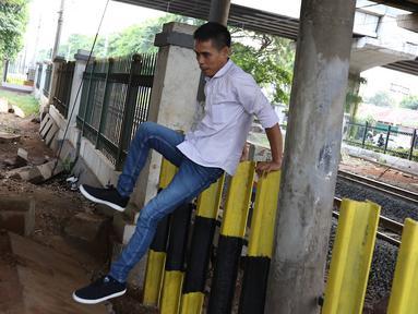 Pejalan kaki melompati pagar perlintasan kereta api di kawasan Tanjung Barat, Jakarta, Senin (7/1). Sejumlah pejalan kaki tetap memilih untuk melompati pagar pembatas dari pada menggunakan fasilitas JPO. (Liputan6.com/Immanuel Antonius)