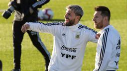 Penyerang Argentina, Lionel Messi berbincang dengan rekannya Sergio Aguero saat mengikuti sesi latihan tim jelang bertanding melawan Brasil di Ciudad Deportiva Antonio Asensio di Palma de Mallorca (12/11/2019). (AFP/Jaime Reina)