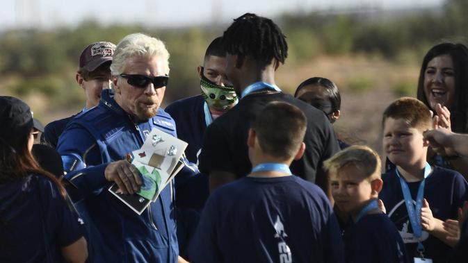 Richard Branson menerima beberapa kartu dari anak-anak saat dia berjalan keluar dari Spaceport America, dekat Truth and Consequences, New Mexico pada 11 Juli 2021 sebelum melakukan perjalanan ke luar angkasa. Patrick T. FALLON / AFP