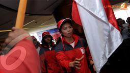 Pebulutangkis Greysia Polii bersiap mencium Sang Merah Putih saat upacara pengukuhan dan pelepasan atlit Sea Games 2013 Myanmar di Jakarta pada 2 Desember 2013 (Liputan6.com/Helmi Fithriansyah)