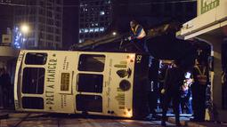 Regu penolong berusaha mengevakuasi trem double-decker yang terbalik di jalan utama di Hong Kong, Kamis (6/4). Belum jelas penyebab kecelakaan, namun kemungkinan akibat pengemudi gagal mengendalikan kendaraan tersebut. (ANTHONY WALLACE/AFP)