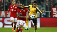 Penyerang Arsenal, Alexis Sanchez berusaha mengontrol bola dari kawalan gelandang Arturo Vidal pada pertandingan 16 besar Liga Champions di Allianz Arena, Munchen, (16/2). Bayern menang telak atas Arsenal dengan skor 5-1. (AFP Photo / Odd Andersen)