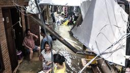 Warga beraktivitas di tengah banjir yang merendam permukiman warga di Kemang Timur XI, Jakarta, Minggu (21/2/2021). Ketinggian air mencapai sepinggang orang dewasa. (merdeka.com/Iqbal S. Nugroho)