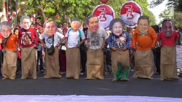 Para warga Solo, Jawa Tengah gunakan topeng para tokoh nasional pada lomba balap karung dalam menyambut HUT RI ke-73.