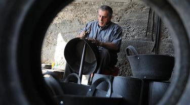 Pria Palestina Mohammed Al-Skafi mengolah sebuah ban kendaraan bekas untuk membuat keranjang penyimpanan di bengkel kerjanya di Kota Hebron, Tepi Barat (10/11/2020). Pria 68 tahun itu membuat dan menjual ember, ikat pinggang, dan keranjang penyimpanan dari ban bekas. (Xinhua/Mamoun Wazwaz)