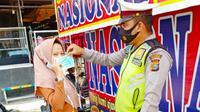 Polisi memberikan masker kepada masyarakat agar disiplin menerapkan protokol kesehatan Covid-19. (Liputan6.com/M Syukur)