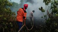Petugas berjibaku memadamkan kebakaran lahan agar tak menimbulkan bencana kabut asap. (Liputan6.com/M Syukur)