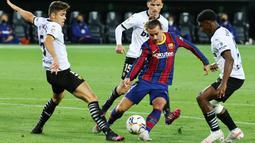Penyerang Barcelona, Antoine Griezmann, berusaha melewari pemain Valencia pada laga Liga Spanyol di Stadion Mestalla, Minggu (2/5/2021). Barcelona menang dengan skor 2-3. (AFP/Jose Jordan)