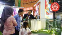 Seorang marketing tengah menjelaskan keunggulan apartemen miliknya ke konsumen dalam pameran properti di Jakarta.