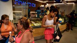 Seorang wanita membeli es krim saat musim panas di Pamplona, Spanyol utara, (2/8). Sebagian wilayah di Spanyol tengah dilanda cuaca ekstrem dengan suhu mencapai lebih dari 40 derajat Celcius (104 Fahrenheit). (AP Photo/Alvaro Barrientos)