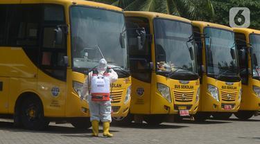 Petugas ber-APD menyemprotkan disinfektan pada bus sekolah di Posko Gabungan PSBB dan Gakplin Protkes, Puskesmas Jatinegara, Jakarta, (22/9/2020). Sejumlah unit bus sekolah kini dialihfungsikan menjadi kendaraan untuk mengantar pasien Covid-19 berstatus OTG menuju Wisma Atlet. (merdeka.com/Imam Buho