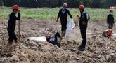 Pekerja Dewan Sipil Raqqa menggali kuburan massal berisi tulang belulang manusia di Raqqa, Suriah, 14 Juli 2019. Di antara jasad-jasad yang ditemukan merupakan warga sipil termasuk perempuan dan anak-anak, demikian juga orang-orang yang diyakini telah ditembak mati oleh militan ISIS. (AP Photo)