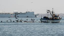 Sebuah kapal nelayan berlayar di dekat kapal rumah sakit Angkatan Laut AS USNS Comfort yang berlabuh di wilayah Piura, Peru, 5 November 2018. Lebih dari 5.000 orang, termasuk imigran Venezuela dirawat oleh personel AS. (ERNESTO BENAVIDES / AFP)