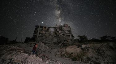 Seorang pria memandangi Galaksi Bima Sakti yang menghiasi langit malam saat dia duduk di antara reruntuhan bangunan akibat pengeboman di Kota Ariha, Provinsi Idlib, Suriah, Sabtu (27/6/2020). (Omar HAJ KADOUR/AFP)