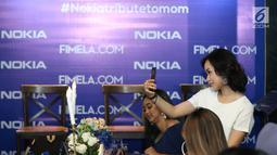 Salah satu selebgram berswafoto saat acara #Nokiatributetomom yang diselenggarakan Fimela.com dan Nokia di Kota Kasablanka, Jakarta, Minggu (27/5). Pihak Nokia memperkenalkan produk terbarunya. (Liputan6.com/Helmi Fithriansyah)