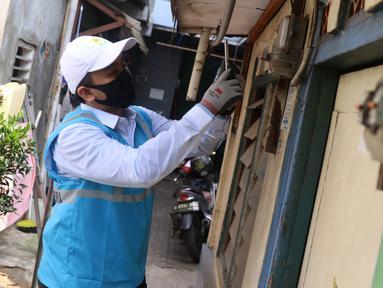 Petugas PLN melakukan pencatatan meteran listrik di rumah warga kawasan Kebayoran Baru, Jakarta, Selasa (30/6/2020). PLN memastikan seluruh petugas dikerahkan mencatat ke rumah pelanggan pascabayar untuk digunakan sebagai dasar perhitungan tagihan listrik bulan Juli 2020. (Liputan6.com/Angga Yuniar)