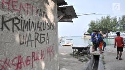 Coretan protes menghiasi salah satu tembok rumah di Pulau Pari, Kepulauan Seribu, Jakarta, Minggu (29/4). Coretan tersebut dibuat oleh para warga yang menolak klaim PT Bumi Pari Asri atas kepemilikan lahan Pulau Pari. (Merdeka.com/Iqbal S. Nugroho)