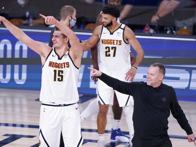 Pebasket Denver Nuggets, Nikola Jokic dan pelatih  Michael Malone, usai menaklukkan Los Angeles Clippers pada gim ketujuh semifinal playoff NBA di Lake Buena Vista, Selasa (15/9/2020).  Nuggets menang dengan skor 104-89. (AP/Mark J. Terrill)