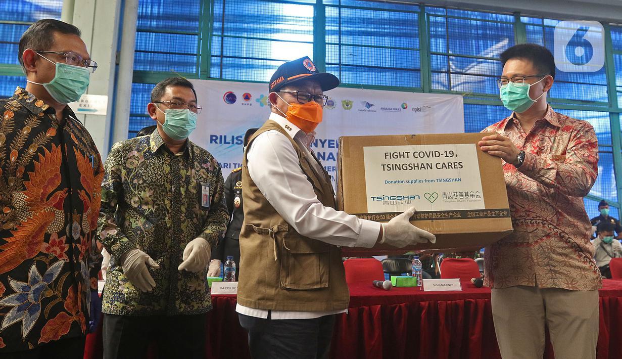 Sestama BNPB Harmensyah secara simbolis menerima bantuan alat kesehatan dari perwakilan investor China di Terminal Kargo 530 Bandara Internasional Soekarno Hatta, Jumat (27/3/2020). Investor China membantu 40 ton alat kesehatan untuk menangani virus corona COVID-19. (Liputan6.com/Herman Zakharia)