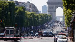 Aparat kepolisian Prancis mengevakuasi jalan Champs Elysees di Paris, Senin (19/6). Seorang pria yang dilengkapi senjata sengaja menabrakkan kendaraannya ke van milik polisi dan kemudian tewas di jalanan ikonik itu. (AP Photo/Matthieu Alexandre)