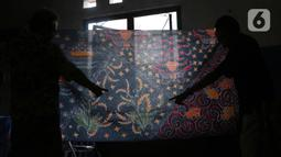 Perajin menunjukkan batik tulis di Sanggar Batik Kembang Mayang, Larangan, Tangerang, Banten, Minggu (19/7/2020). Rata-rata, lama pembuatan untuk selembar batik tulis adalah sekitar sebulan. (Liputan6.com/Angga Yuniar)