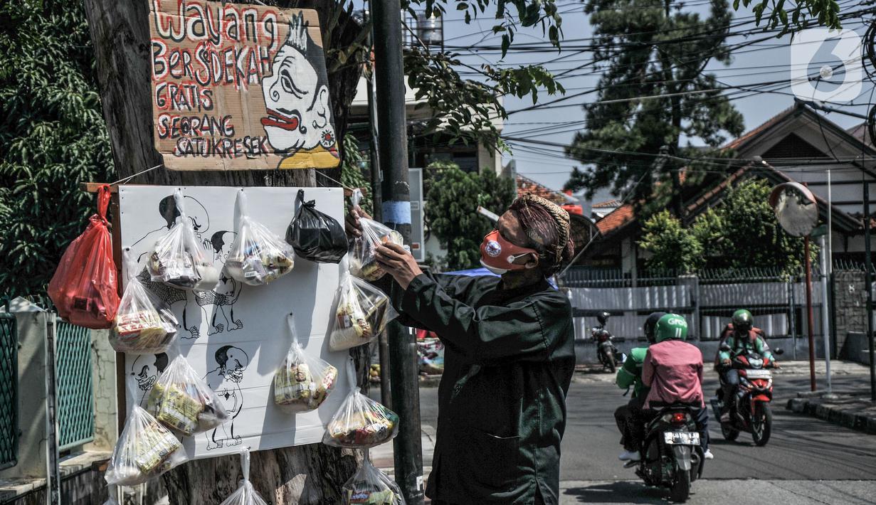 "Iskandar (59) menyiapkan paket sembako ""Sedekah Cantholan"" di kawasan Cawang, Jakarta Timur, Selasa (27/7/2021). Berawal dari niat membantu masyarakat di tengah pandemi Covid-19, Iskandar menggelar ""Sedekah Cantholan"". (merdeka.com/Iqbal S Nugroho)"