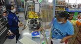 Pekerja melayani pembeli dari balik plastik pembatas pada sebuah minimarket di kawasan Cinere, Depok, Jawa Barat, Rabu (8/4/2020). Penggunaan plastik pembatas tersebut bertujuan untuk mengantisipasi penyebaran virus corona atau COVID-19 sebagai bentuk social distancing. (merdeka.com/Arie Basuki)