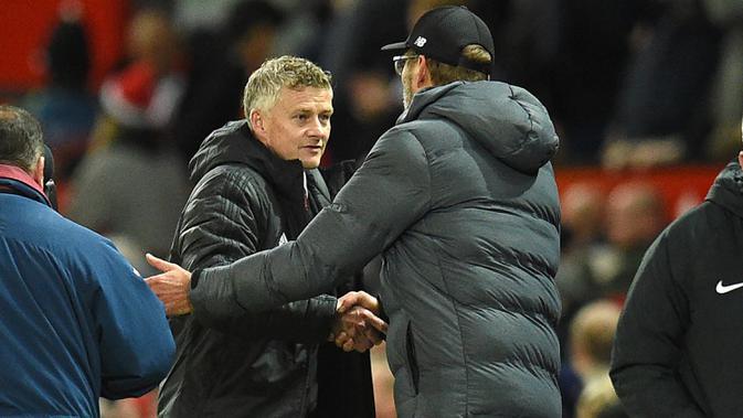 Pelatih Manchester United, Ole Gunnar Solskjaer, bersalaman dengan pelatih Liverpool, Jurgen Klopp, usai laga Premier League di Stadion Old Trafford, Manchester, Minggu (20/10). Kedua klub bermain imbang 1-1. (AFP/Oli Scarff)