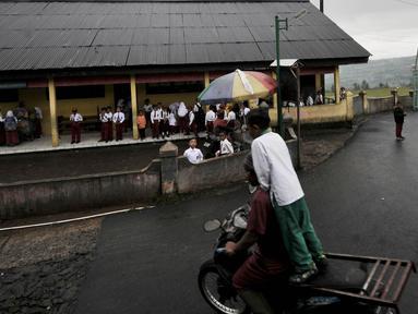 Siswa bermain di halaman sekolah dengan latar belakang pemandangan Gunung Sindoro yang tertutup kabut sebelum dimulainya kegiatan belajar di Gedung Sekolah Dasar (SD) Negeri 2 Bowongso, Kecamatan Kalikajar, Wonosobo, Jawa Tengah (2/4). (merdeka.com/Iqbal S. Nugroho)