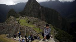 Seorang wanita tampak berfoto dengan pemandangan reruntuhan Kerajaan Inca di Pegunungan Machu Picchu , Peru, Rabu (12/8/2015). Pemerintah setempat membatasi wisatawan yang masuk ke Machu Picchu yang hanya menerima 2.500 wisatawan. (REUTERS/Pilar Olivares)