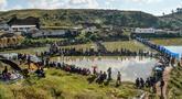 Para peserta pria berkonsentrasi dengan kailnya pada kompetisi memancing di sebuah kolam dekat desa Weilei di Negara Bagian Meghalaya, timur laut India, Sabtu (21/9/2019). Ratusan peserta berpartisipasi dalam kompetisi yang memperebutkan sejumlah hadia tersebut. (DIPTENDU DUTTA / AFP)