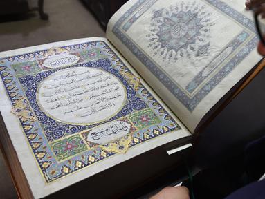 Seorang seniman Afghanistan, Mohammad Tamim Sahibzada menunjukkan Alquran buatan tangan di Mourad Khani, Kabul, Afghanistan (19/4). Kitab suci Alquran ini dibuat dengan tangan secara manual di atas kain sutra. (AFP/Wakil Kohsar)