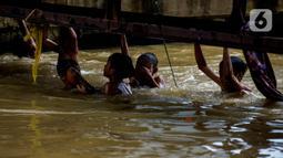 Sejumlah anak bermain dan berenang di aliran Kalimalang, Jakarta, Sabtu (15/2/2020). Cuaca yang tidak menentu membuat aliran air terkadang menjadi deras sehingga akan membahayakan keselamatan anak-anak saat bermain dan berenang. (merdeka.com/Imam Buhori)