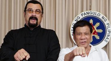 Presiden Filipina, Rodrigo Duterte (kanan) menunjukkan pukulan tinju bersama aktor laga Hollywood, Steven Seagal yang sedang melakukan kunjungan kehormatan di Istana Kepresidenan Malacanang di Manila, Kamis (12/10). (Handout/PPD/AFP)