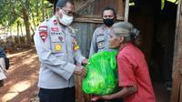 Foto : Wakapolda NTT, Brigjen Pol. Johni Asadoma saat menggelar aksi sosial bagi warga terdampak covid-19 di Kabupaten Kupang, NTT (Liputan6.com/Ola Keda)