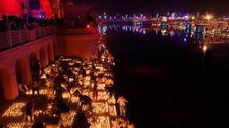 Masyarakat India menyalakan lampu dari tanah liat pada festival Diwali di tepi Sungai Sarayu, Ayodhya, Selasa (6/11). Kota di utara India itu memecahkan rekor dunia Guinness setelah menyalakan 300.150 lampu selama 45 menit. (AP/Rajesh Kumar Singh)