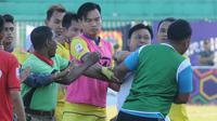 Pelatih Persik Kediri, Budihardjo Thalib berusaha melerai pertikaian antarpemain saat melawan Madura FC di Stadion Ahmad Yani Sumenep, Jumat (2/8/2019). (Bola.com/Gatot Susetyo)