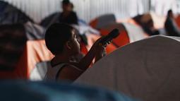 Seorang anak imigran bermain di luar tenda tempat penampungan di Tijuana, Meksiko 6 April 2019. Rombongan migran Amerika Tengah mencapai kota perbatasan antara Meksiko dan AS tersebut  untuk mencari suaka akibat kekerasan, pembunuhan dan kemiskinan yang mengancam mereka. (REUTERS/Carlos Jasso)